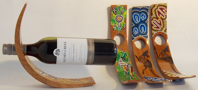 C-shaped wine bottle holders decorated in Aboriginal contemporary art and traditional dot art style